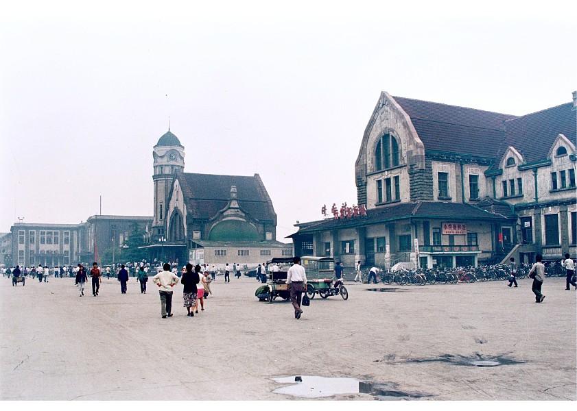 """济南火车站建于19世纪末二十世纪初,由德国著名建筑设计师赫尔曼菲舍尔设计制造的一座典型的哥特式车站建筑。济南铁路建设初期共有两座火车站:一个是1908年始建的津浦铁路济南站一个是1914-1915年建设的胶济铁路济南站,20世纪30年代前这两座火车站同时使用。1937年""""七七事变后侵华日军为了管理方便将原来的胶济站并入津浦站,就是人们心中的济南老火车站。1992年7月1日济南老火车站钟楼的机械钟永远停止了运行。照片拍摄于1992年6月拆前,出站口地面上已开始进行地质钻探。照片是:火车站钟楼、售票"""