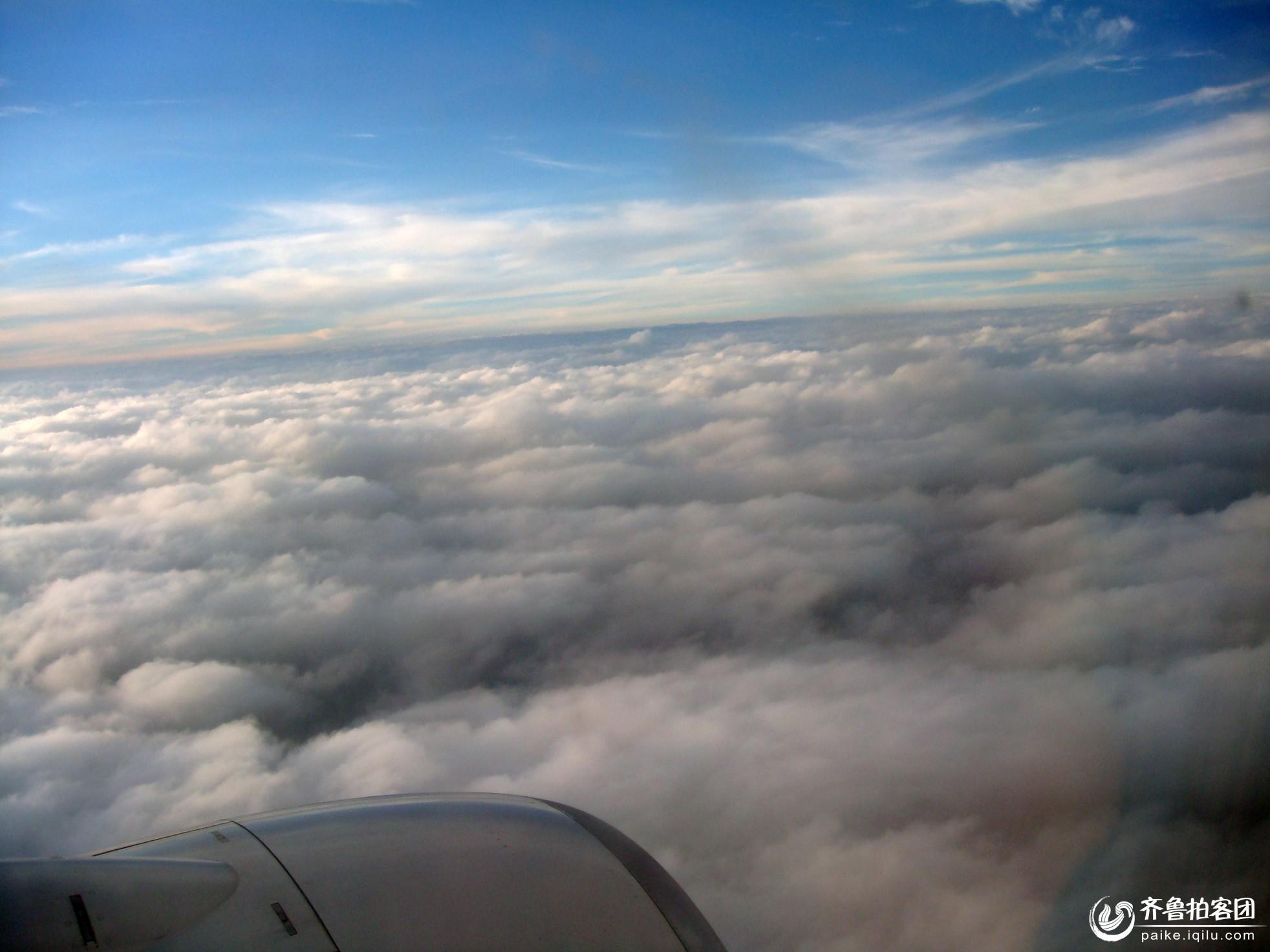 从郑州坐飞机到昆明,有幸在天上看到了梦幻一般的云。这姿态万千,绝美无双的云让我惊叹不已。那云朵一层一层地叠在一起,像连绵不绝的山峰,像翻涌的波涛,天蓝的如同一颗巨大蓝宝石,云白得没有一点污渍。 太阳西下了,照在云朵上,把大片的云映照得如同镀上了一层薄薄的金,天边仿佛在迅速燃烧,我忽然觉得被笼罩在一种奇丽的景色之中,恍如置身于金光万道滚红霓的天宫。