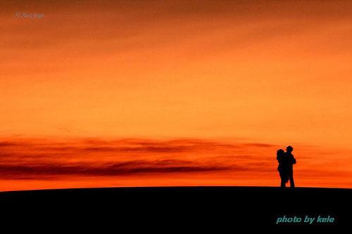 摄影师巧用剪影,在红色的夕阳下,情侣相互拥抱的影子,让人感觉无限