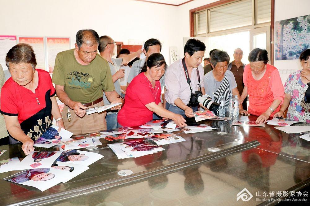 省摄影家协会秘书长张世刚为村民分发照片
