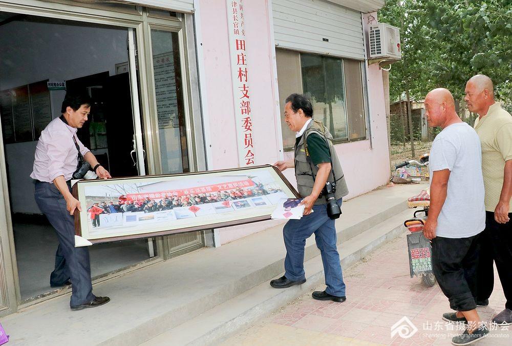 省摄影家协会秘书长张世刚等为村民赠送照片
