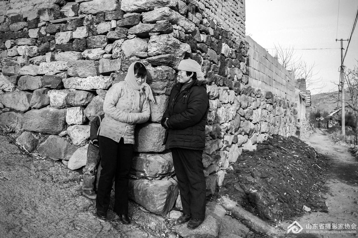 2008年2月11日,沂水县小崮头村的妇女倚在墙角拉呱。.jpg