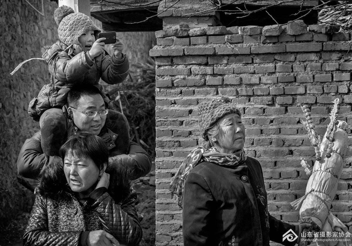 2014年正月里,沂水县大峪村几位群众站在村口看演出。.jpg