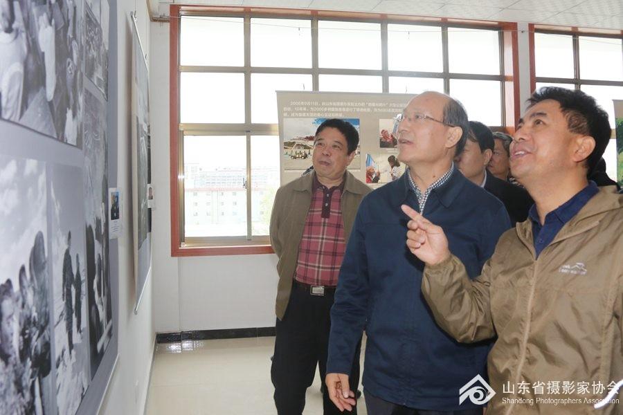 8月27日,山东省摄协副主席范长国(右一)向季缃绮副省长(右二)介绍展览。 ... ...