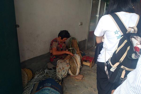 草碾村村民正在自家门前完成草编的制作。