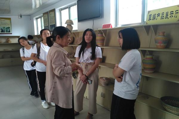 在草碾产品展示区,负责人正向队员们介绍草编的原料选取与制作过程。