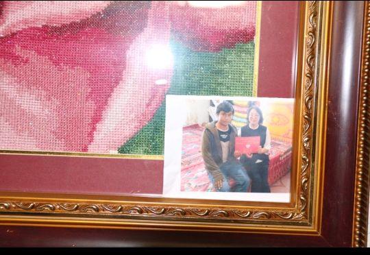 """受访者家中展示的与自己""""结对子""""的汉族亲戚照片。 徐心蕾 摄"""