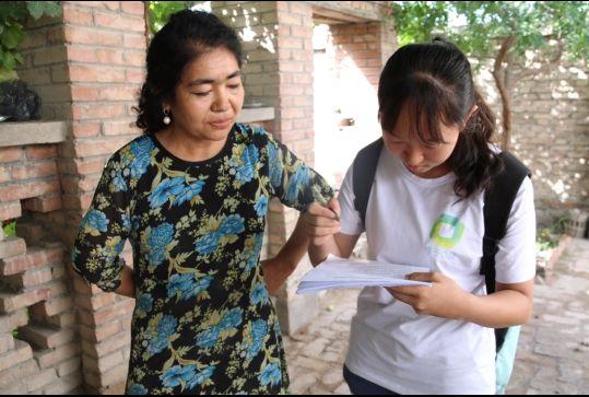 调研队员闫如玉(右)帮助汉字基础不好的受访群众填写调查问卷,真实表达每一位受访者内心意愿。 徐心蕾 摄 ...