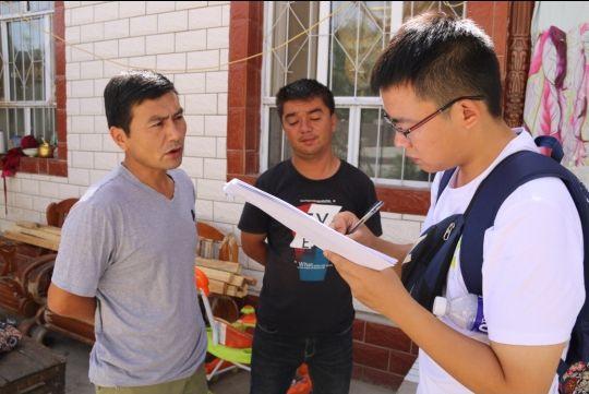 基层干部艾买提(左)帮助汉语水平不高的受访群众(中)翻译调研队员的语句。 徐心蕾 摄 ...