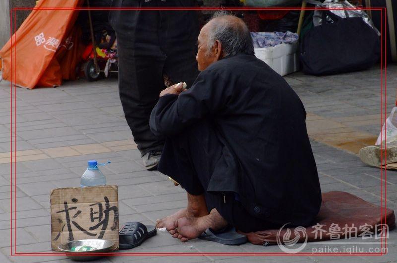 身着破烂不堪,脏兮兮的衣服,坐在马路边上,靠手里拿着的那只碗来乞讨